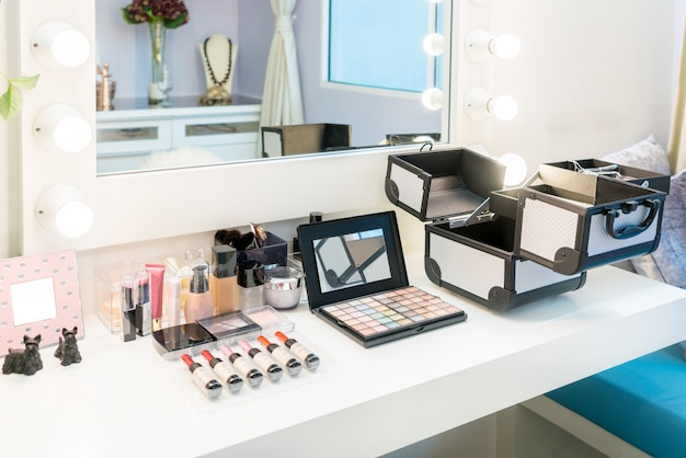 Cosmetic set with eye shadow, eye liner and powder on wood dressing table in home.