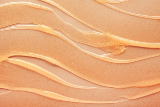 Cosmetic shimmering oil gel golden yellow texture background