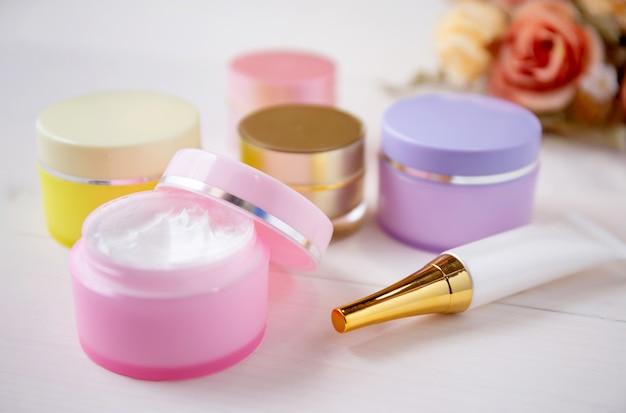 Cosmetic and skin care product and flower on white wood table