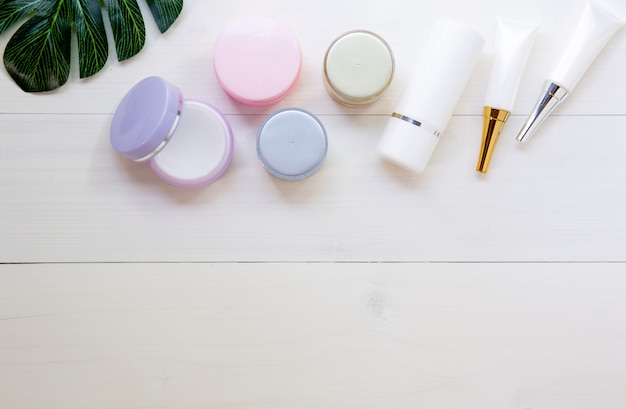Cosmetic and skin care product and green leaves on white wood table