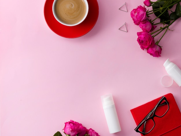 Cosmetic skin care product, notebook, coffee and flowers on pink