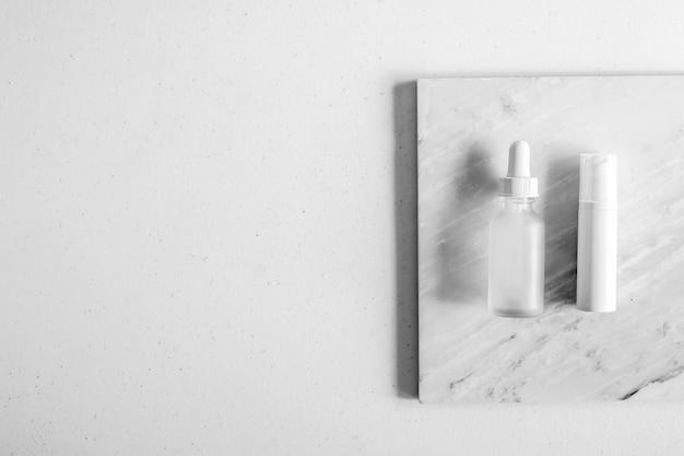 Косметическая упаковка для ухода за кожей. косметический продукт макет на роскошный белый мрамор с естественным освещением и тенью.