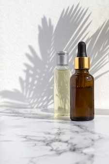 Cosmetic skincare products on marble background with palm leaves shadow.