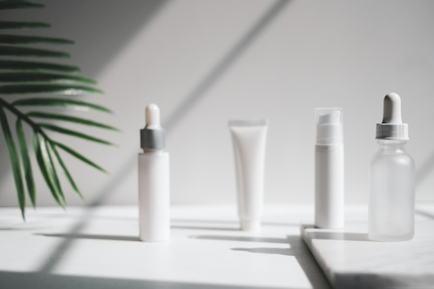 Cosmetic skincare serum . beauty product mock up on luxury white marble with natural light and shadow.