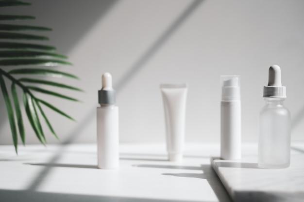 Косметическая сыворотка для ухода за кожей. косметический продукт макет на роскошный белый мрамор с естественным освещением и тенью.
