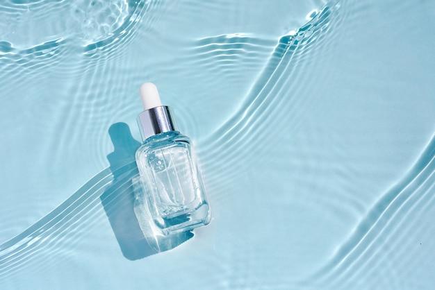 Косметический спа-уход за кожей, стеклянная бутылка с сывороткой, мицеллярный тоник с коллагеном на голубой воде с волнами. рекламная медицинская сыворотка для антивозрастного ухода, увлажнения и очищения