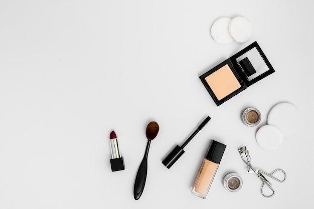 Cosmetic sponges; compact powder; foundation; lipstick eyeshadow; eyelash curler and brushes on white background
