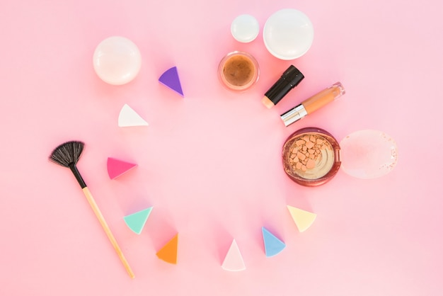 Cosmetic sponges of different colors with make-up products on pink background