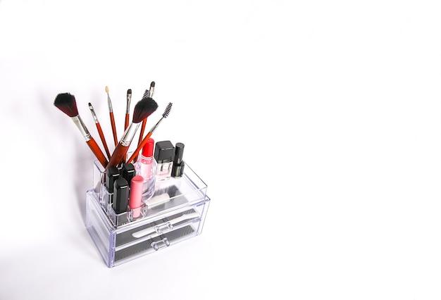 화장품 보관. 화장품 브러시와 립스틱이 있는 투명 상자