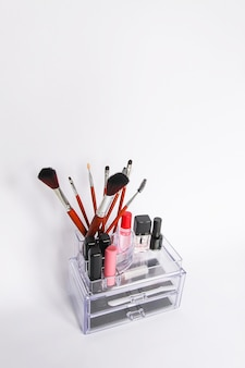 Cosmetic storage. transparent box with cosmetics brushes and lipsticks