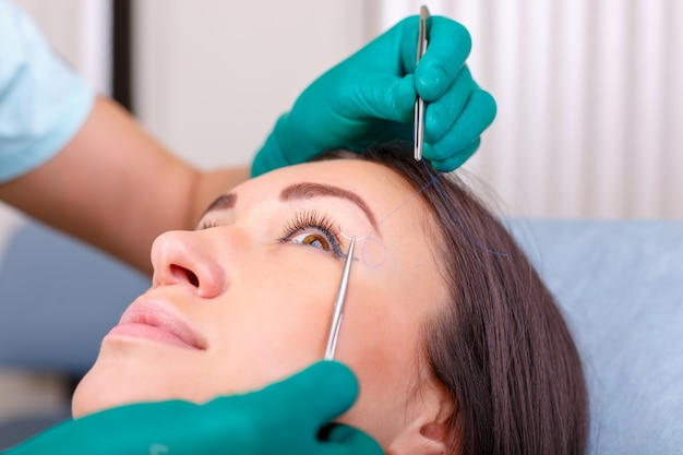 Cosmetic surgeon examining female client in clinic before plastic surgery