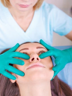Cosmetic surgeon examining female client in clinik  before plast