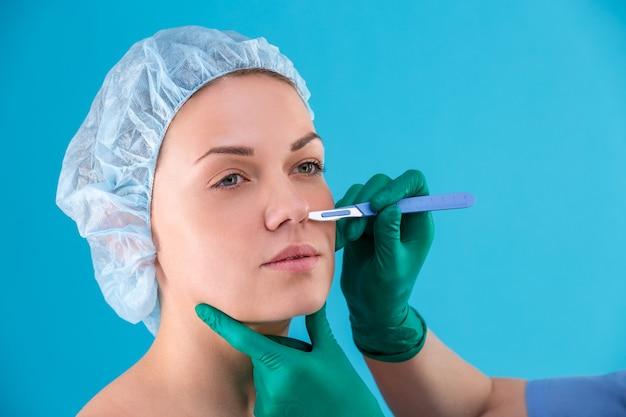 オフィスで女性のクライアントを調べる美容整形外科医。女性の顔、整形手術前のまぶた、眼瞼形成術をチェックする医師。女性の顔に触れる外科医または美容師の手。鼻形成術