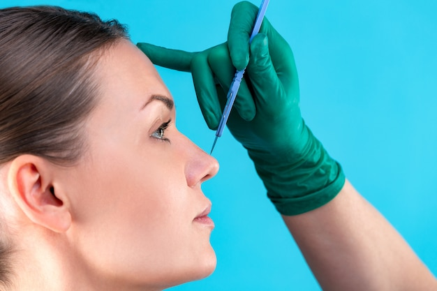 성형 외과 의사 사무실에서 여성 고객을 검사입니다. 의사 검사 여자의 얼굴, 성형 수술 전에 코. 여자 얼굴을 만지고 외과 의사 또는 미용사 손. 코 성형술