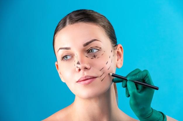 Косметический хирург, исследующий клиентку в офисе