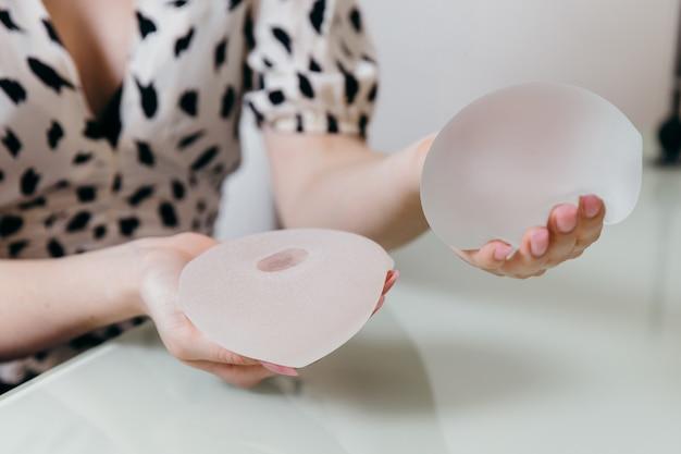 Косметический хирург показывает образцы грудных имплантатов пациентке и рассказывает о ее будущей операции