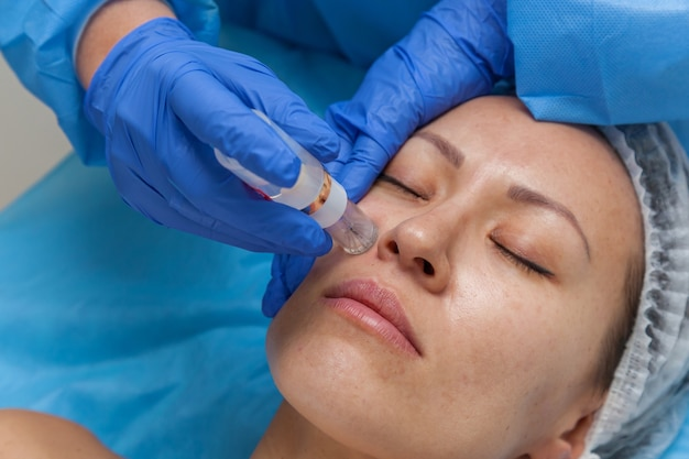 Cosmetic treatment by injection in the clinic use of a dermal injector to stimulate the skin