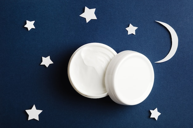 Cosmetic white container on night sky background top view.