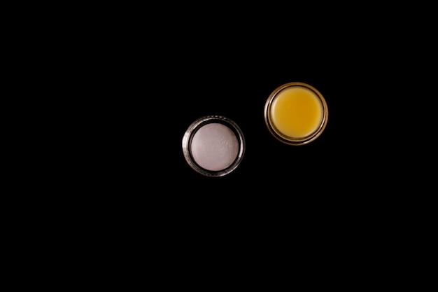 黒の背景に毎日のスキンケアのための他のメーカーからの化粧品の黄色い香油。スキンケア製品のコンセプト