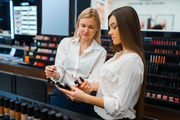 美容師は、化粧品店のショーケースで女性にアドバイスします。高級美容院サロン、ファッション市場の女性客と美容師