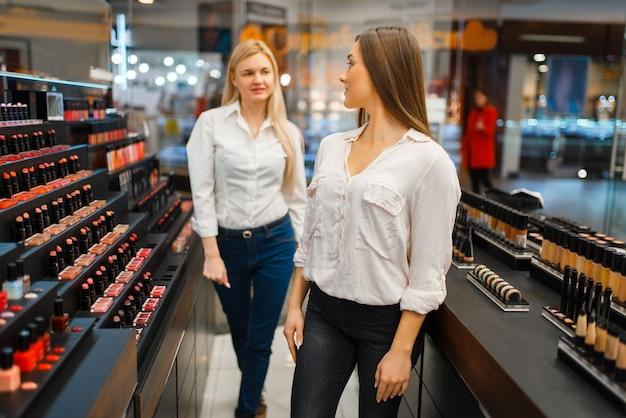 化粧品店のショーケースで口紅を選ぶ美容師と女性。高級美容院サロン、ファッション市場の女性客と美容師