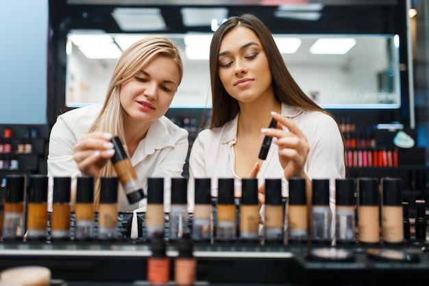 化粧品店のショーケースでマニキュアを選ぶ美容師と女性。高級美容院サロン、ファッション市場の女性客と美容師