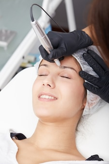 Cosmetician apply permanent make up on eyebrows
