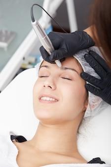 Косметолог наносит перманентный макияж на брови