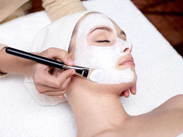 스파 살롱에서 젊은 아름다운 여성을위한 얼굴 미용 마스크를 적용하는 미용사