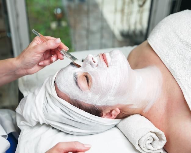 スティックで女性の顔に顔のマスクを適用する美容師