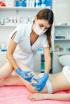 Cosmetician gives botox injection in the thigh