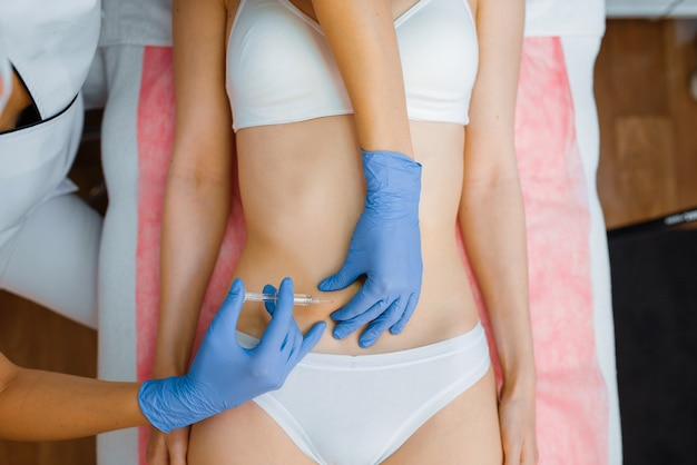 Cosmetician in gloves gives botox injection in the stomach to female patient on treatment table. rejuvenation procedure in beautician salon. doctor and woman, cosmetic surgery against wrinkles