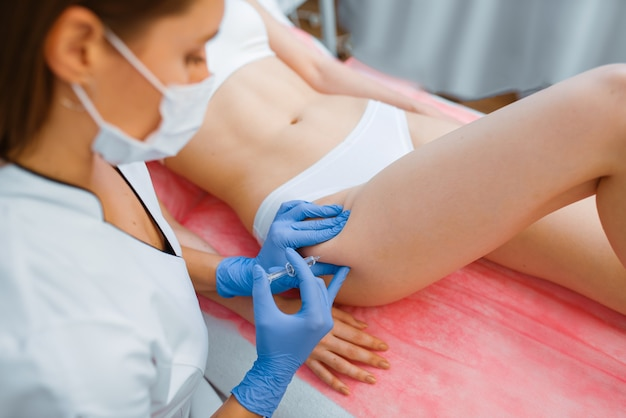 Cosmetician in gloves gives botox injection in the thigh to female patient on treatment table. rejuvenation procedure in beautician salon.