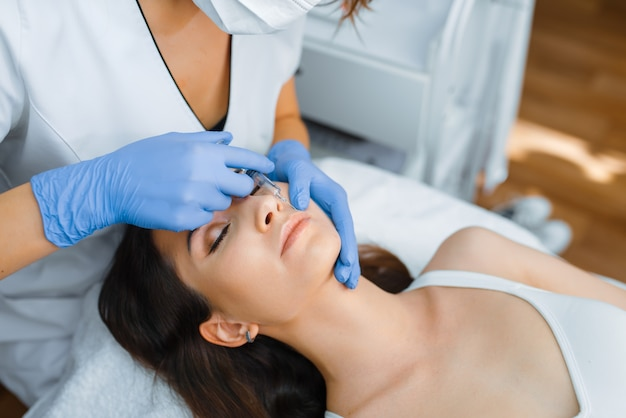 Cosmetician in gloves gives face botox injections to female patient on treatment table. rejuvenation procedure in beautician salon. doctor and woman, cosmetic surgery against wrinkles