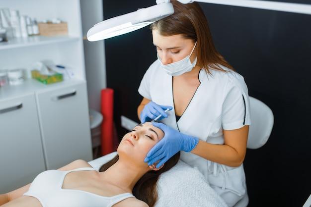 Косметолог в перчатках и пациентка на лечебном столе. процедура омоложения в салоне косметолога. врач и женщина, косметическая хирургия против морщин