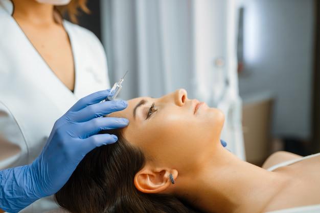 手袋の美容師は、ボトックス注射、治療テーブルの上の女性患者と注射器を保持しています。美容サロンでの若返りの手順。医師と女性、しわに対する美容整形
