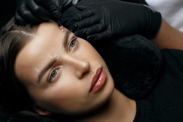 眉毛の恒久的な手順の前に白いマークアップを作る手袋の化粧品