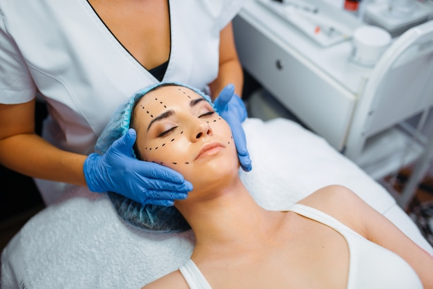 Cosmetician makes botox injection in dotted lines on female patient face, botox injections preparation. rejuvenation procedure in beautician salon. cosmetic surgery against wrinkles and aging