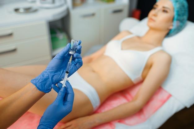 美容師は、治療テーブルの上の女性患者にボトックス療法を行います。