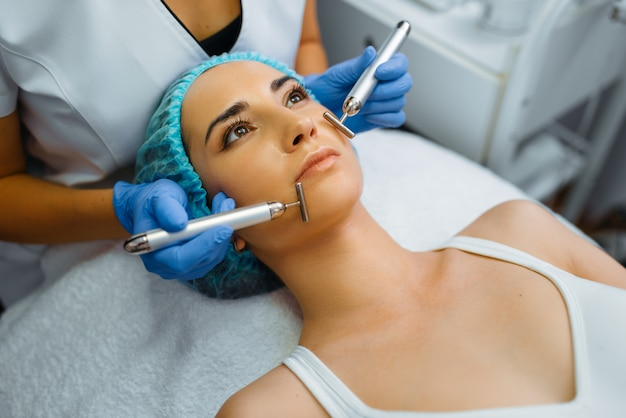 美容師は女性患者の顔を滑らかにします