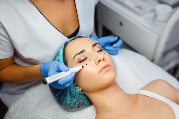 Косметолог с маркером наносит пунктирные линии на лицо пациентки, препарат для инъекций ботокса. процедура омоложения в салоне косметолога. косметическая хирургия против морщин и старения