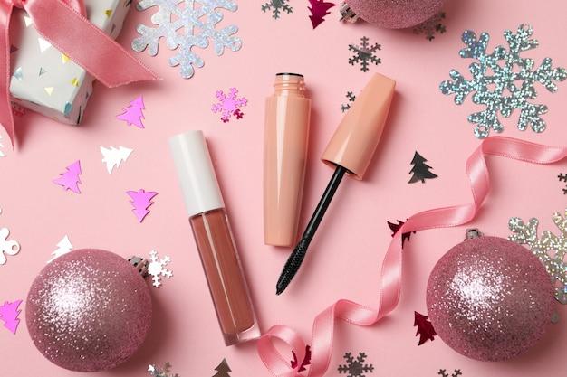ピンクの背景に化粧品とクリスマスアクセサリー