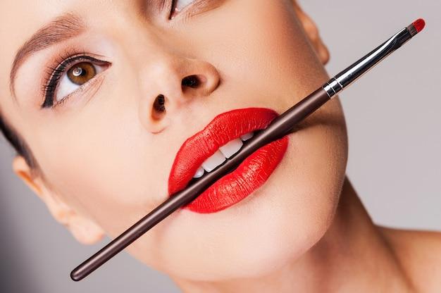 化粧品の芸術性。彼女の口にmake-u [pブラシを保持し、灰色の背景に立っている間目をそらしている赤い唇を持つ美しい女性のクローズアップ