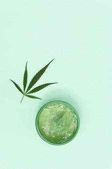 대마초를 기본으로 한 화장품, 바디 크림 또는 젤이 든 항아리 및 대마초의 천연 잎. 대마 잎 화장품