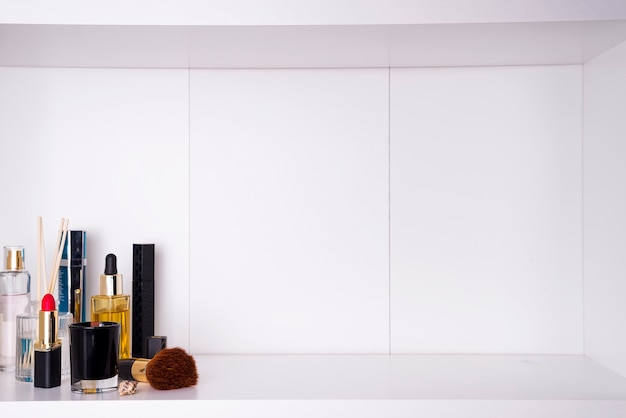 Cosmetics in bathroom on a white bathroom shelf