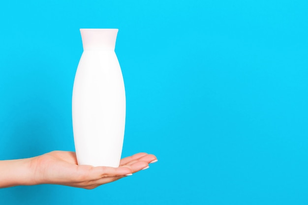 Cosmetics bottle in female hand