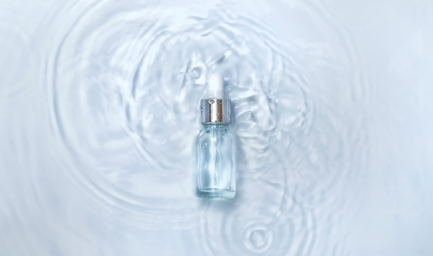 Cosmetics in a bottle in water, skin hydration concept. hyaluronic acid. selective focus. nature.
