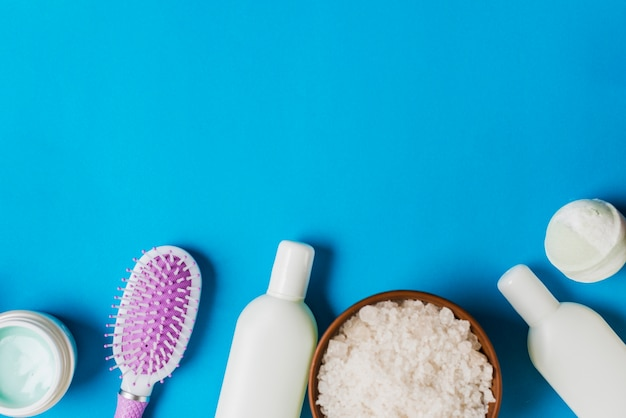 Cosmetics bottles; cream; hairbrush and salt on blue backdrop