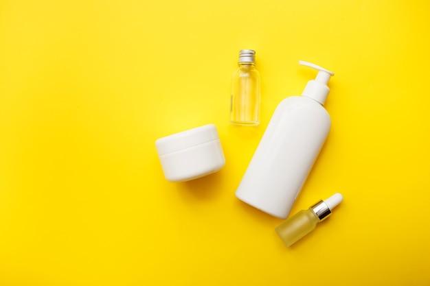 明るい黄色の背景、平面図、コピースペースに化粧品ボトル。モックアップ。白い瓶、バスアクセサリー。顔と体のケアの概念。