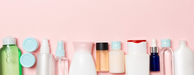 Cosmetics bottles on pink background